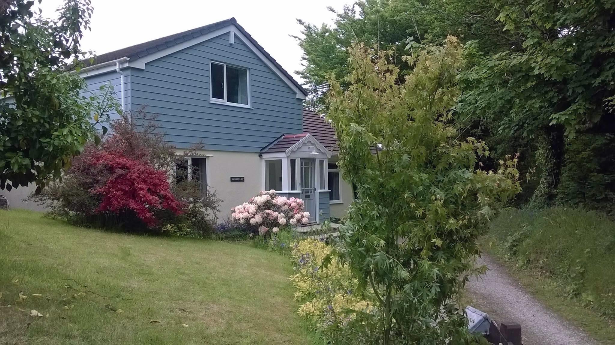 a blue house in a beautiful garden